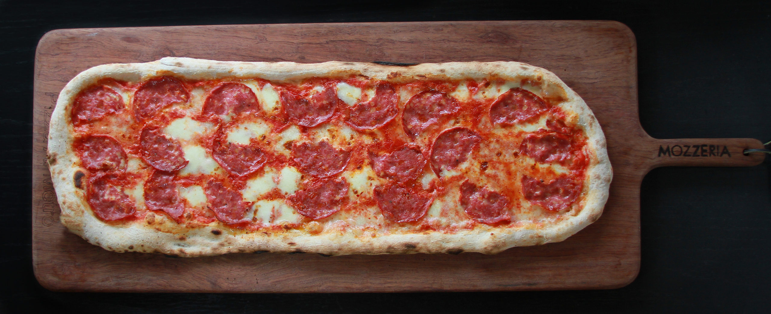 A long rectangle pepperoni pizza sitting on wooden peel